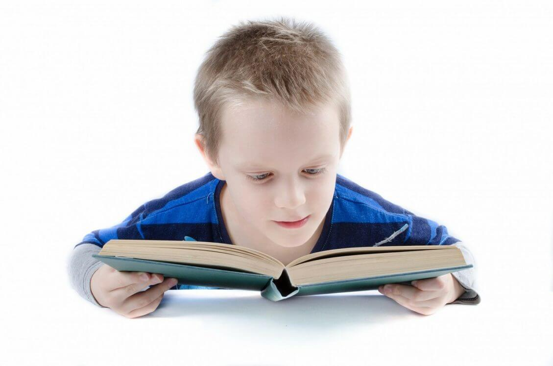 Front view of boy's face looking down at the book he is holding.