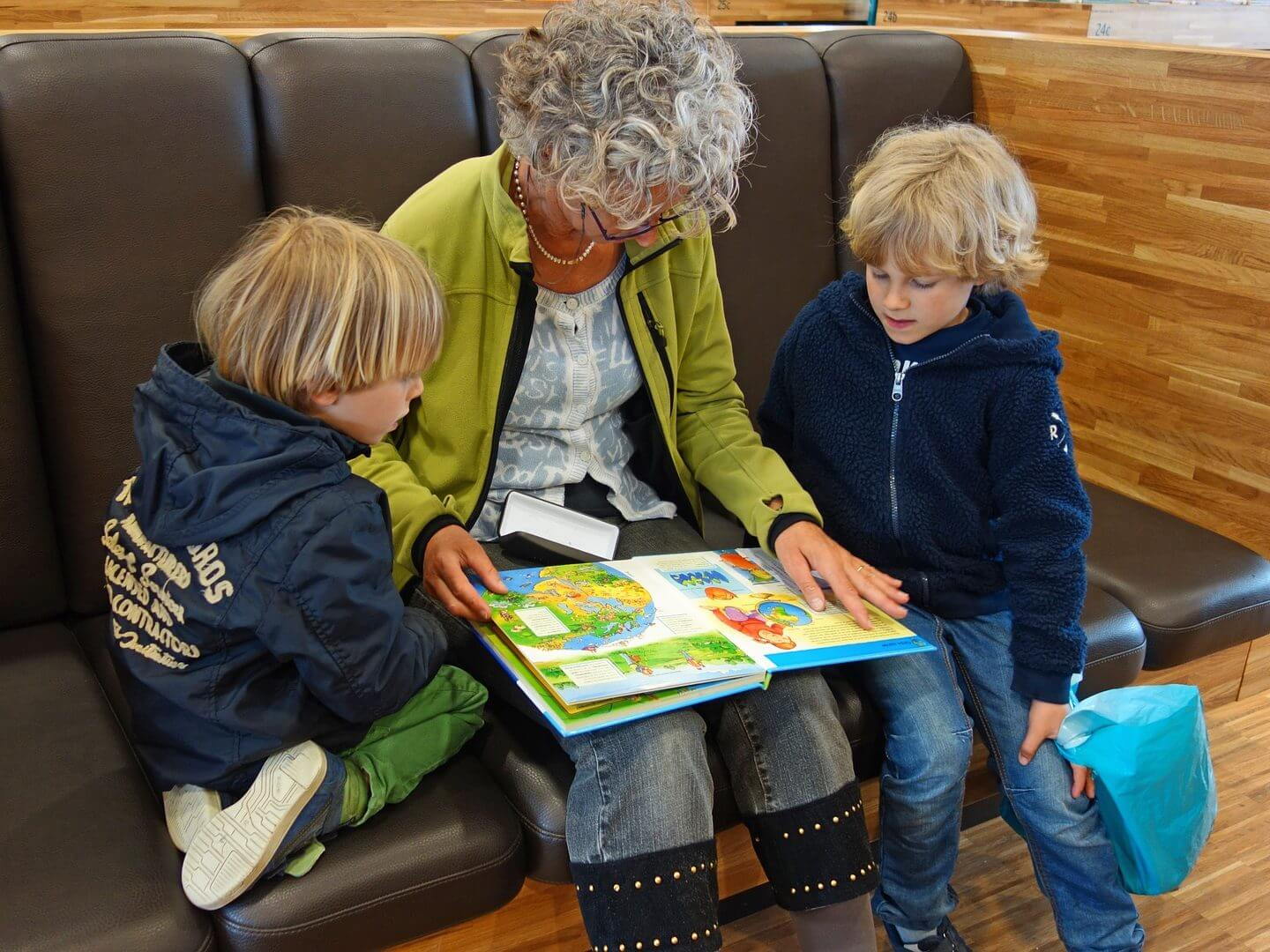 Two young boys sitting beside Grandma who is pointing to words in a picture book..