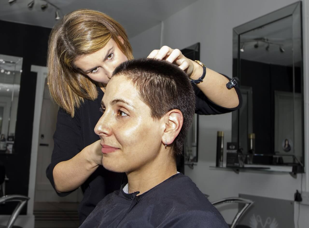 Lady hairdresser cutting client's hair.
