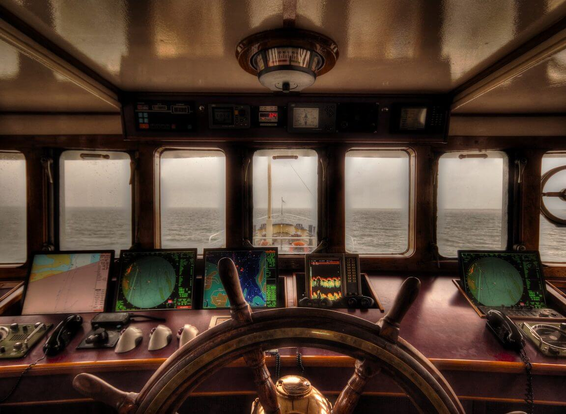 The bridge of a ship with steering wheel and navigation aids.