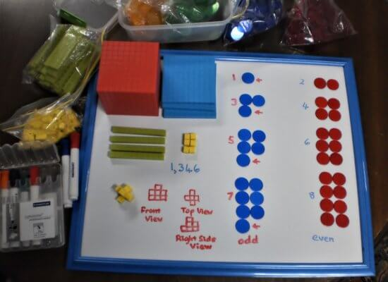 Counters laid out on a whiteboard showing odd and even numbers from 1 to 8; base 10 blocks representing 1,346 andcubes being used to model a 3D shape from which 2D front, top and right-side views have been drawn.